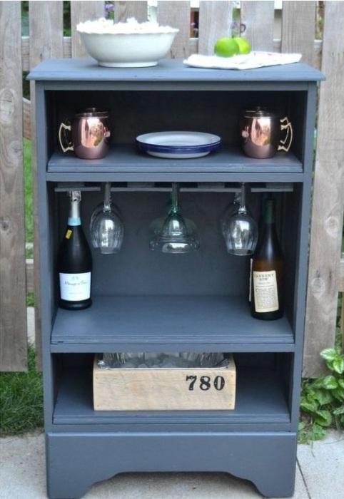 Открытый мини-бар в сером цвете, который создан из старой деревянной тумбочки.