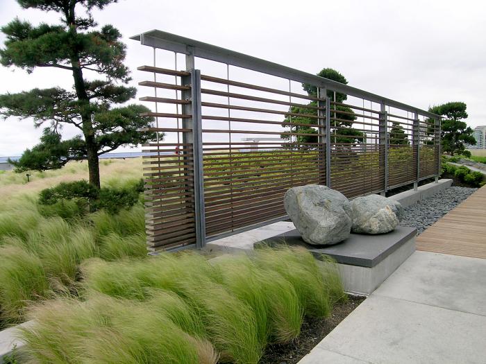 Деревянная перегородка по типу жалюзи отлично впишется в современный ландшафтный дизайн.