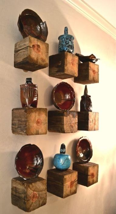 Нескучные декоративные полки в виде квадратных брусков из тёмной породы древесины на фоне светлой стены.