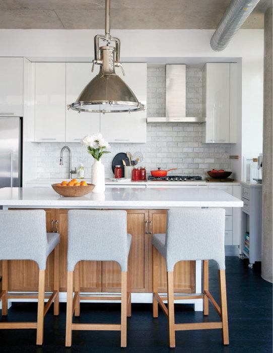 Необычная люстра в индустриальном стиле и множество деревянных элементов - очевидные решения для оживления интерьера светлой кухни.