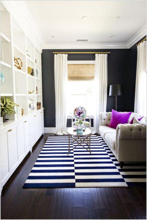 Полосатый ковер, который визуально расширяет пространство гостиной комнаты.