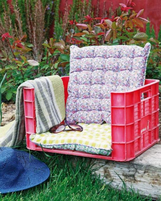 Кресло из старого пластмассового ящика, которое можно использовать для украшения веранды или беседки.
