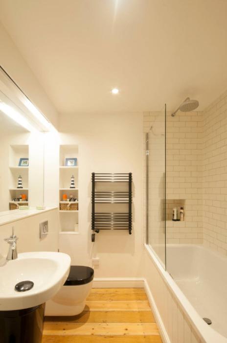 Деревянный пол в современном интерьере ванной комнаты - непривычное, но вполне практичное решение.