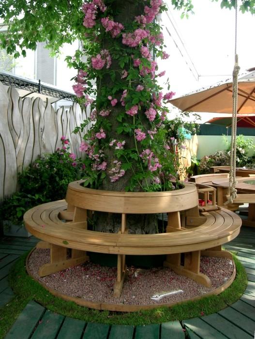 Оригинальная деревянная скамейка, расположенная вокруг дерева.