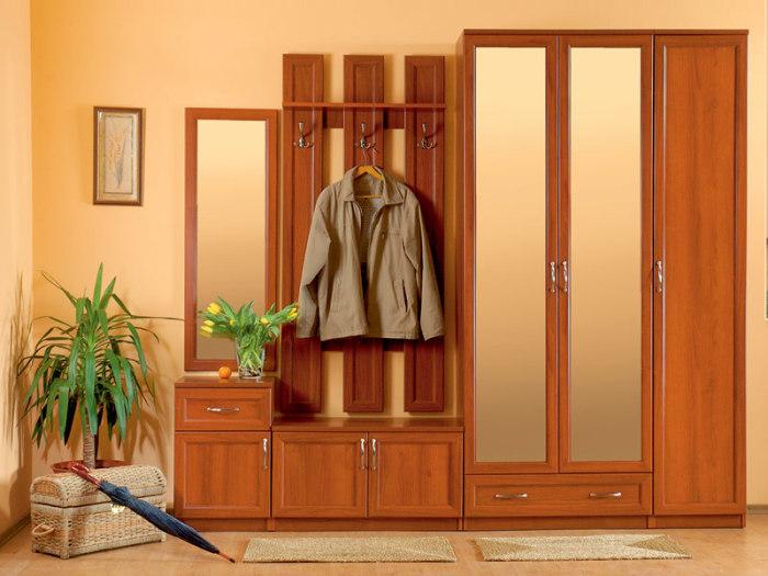 Простой трехстворчатый шкаф из светлой породы древесины.