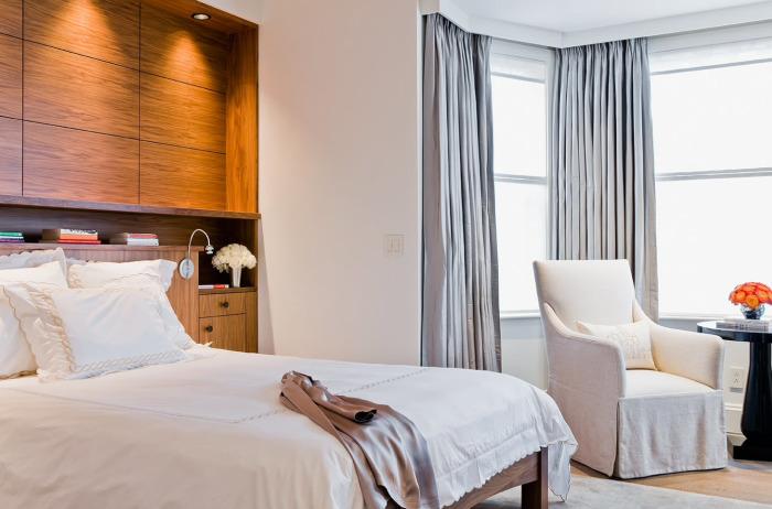 Традиционная спальная комната в минималистском стиле с применением преимущественно светлых оттенков, которые способствуют визуальному увеличению пространства.