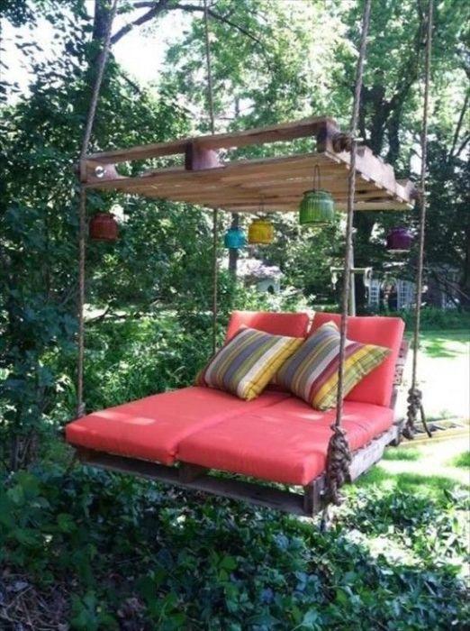 Подвесная кровать из деревянных поддонов значительно экономящая пространство на дачном участке.