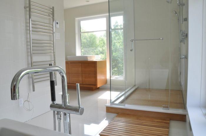 Шикарное сочетание стекла и дорогой древесины в интерьере ванной комнаты.