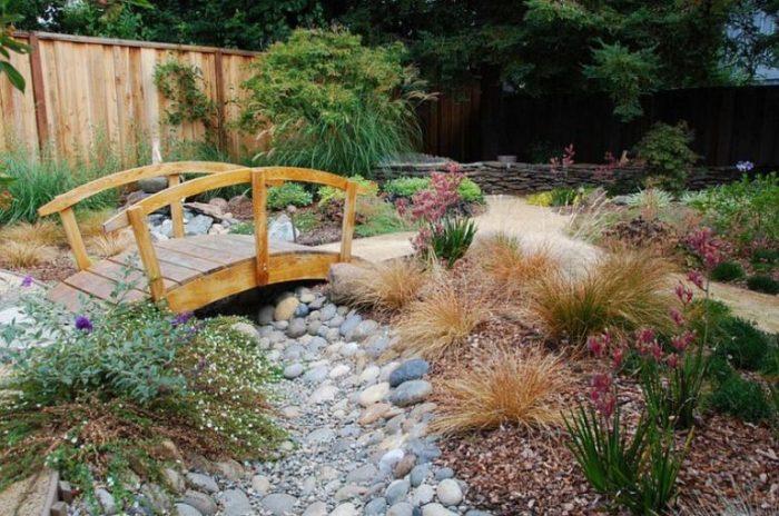 Классическая конструкция деревянного мостика через каменный пруд в саду.