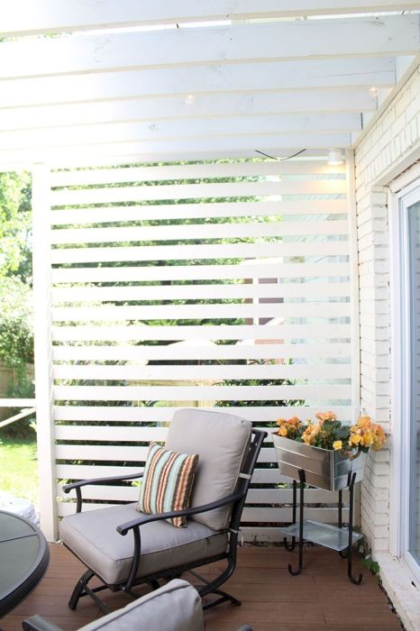 Стильное патио с обеденным столиком и уютной площадкой, обшитой покрашенным белым деревом.