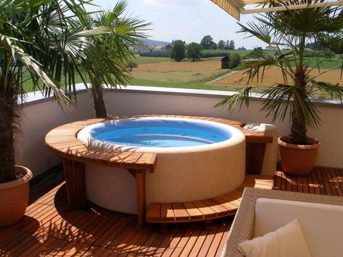 Гидромассажный спа-бассейн круглой формы во дворе частного дома.