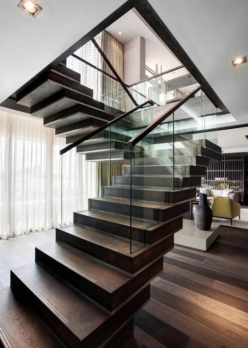 Классическая лестница со стеклянными перилами, выполненная без излишеств, в строгом соответствии с интерьером загородного дома.