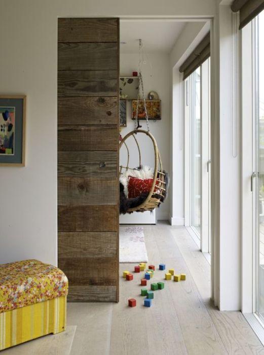 Состаренная деревянная межкомнатная дверь с раздвижным механизмом, который вмонтирован в стену.