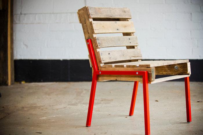 Кресло из деревянного поддона с металлическими ножками, которые покрашены в яркий красный оттенок.