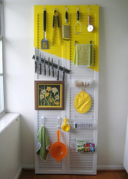 Из старой жалюзийной двери, покрашенной в ярко-жёлтый и светлый оттенок, может получится функциональный органайзер для хранения сковородок, полотенец и мелких кухонных принадлежностей.