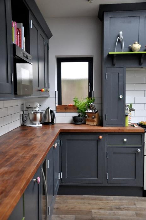 Традиционный образец современного кухонного интерьера с деревянной столешницей и тёмной модульной гарнитурой.