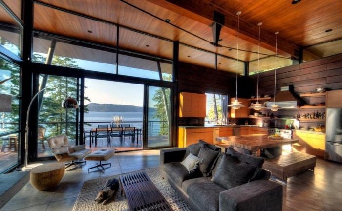 Просторная гостиная комната, оформленная в коричневых тонах с небольшим количеством серой и светлой мебели.