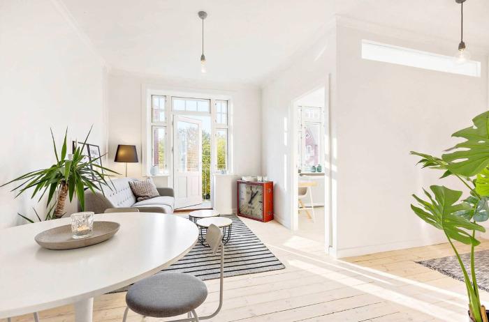 Просторная светлая гостиная комната, совместившая в себе мягкий серый диванчик, необычную тумбочку в форме часов и круглый обеденный стол.