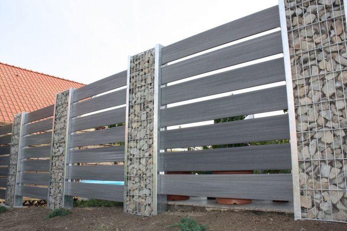 Сетчатая конструкция как основание для панельного деревянного забора из темной породы древесины.