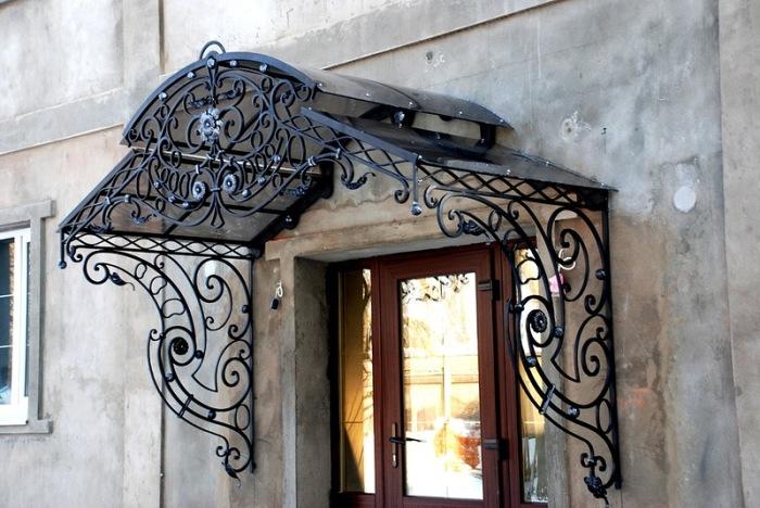 Кованый козырек для крыльца - главное украшение входа в загородный дом.