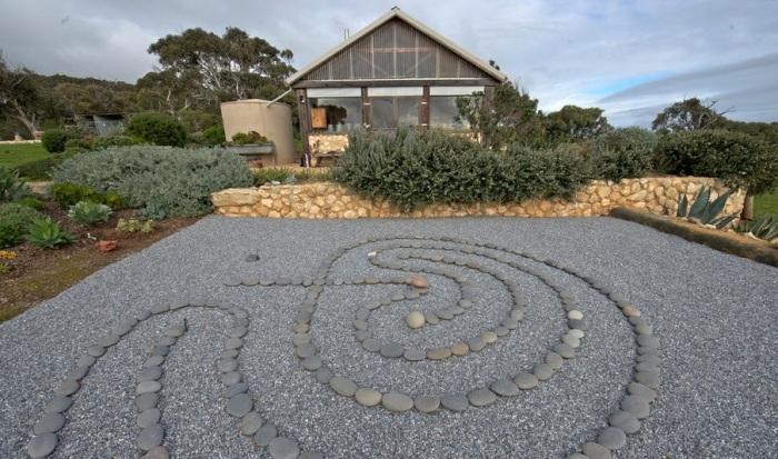 Узор из камней на гравийной площадке квадратной формы.