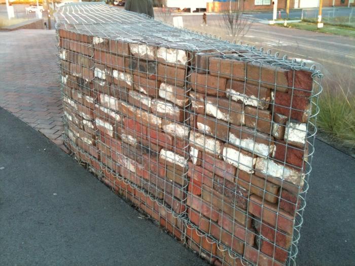 Забор из габионно-сетчатого изделия заполненного кирпичами.