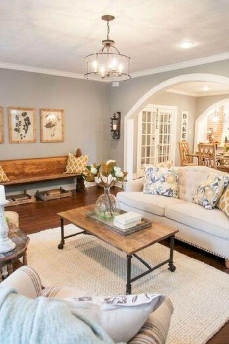 Стильная просторная гостиная комната с небольшим светлым диваном, множеством деревянных элементов и журнальным столиком на колёсиках.