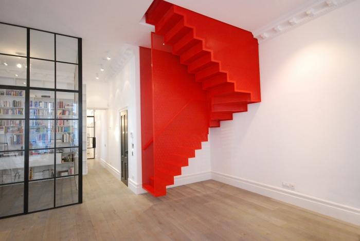Немного измененный классический дизайн лестницы ярко красного оттенка станет явным дополнением к современному интерьеру.