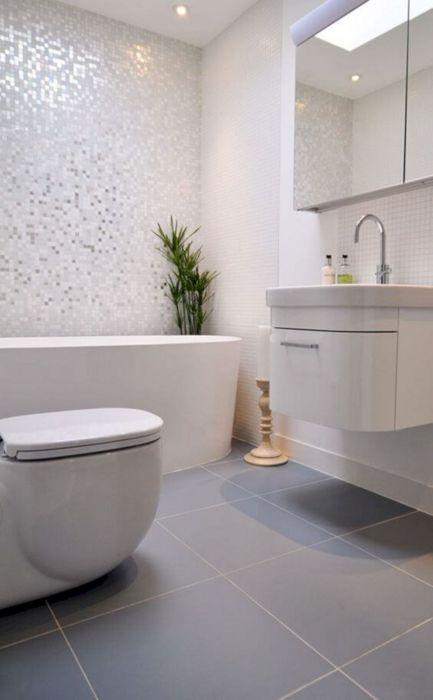 Серебристая плитка в виде мозаики в сочетании с другими монохромными поверхностями позволит визуально расширить пространство ванной комнаты.