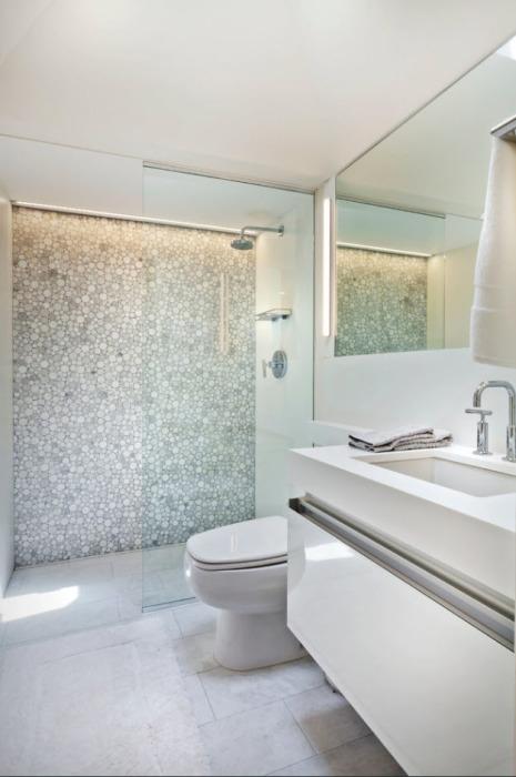Шикарная туалетная комната может похвастаться массивной стеной из дорогой керамической плитки круглой формы.