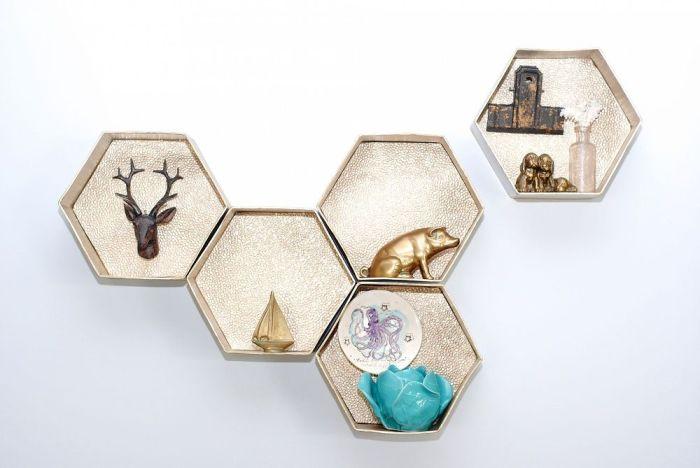 Оригинальные полки, сделанные из золотистых подарочных шестиугольных коробочек из-под шоколадных конфет, прикрепленных к стене.