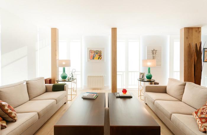 Светлая гостиная комната, разделенная на две части с помощью классических деревянных перегородок.