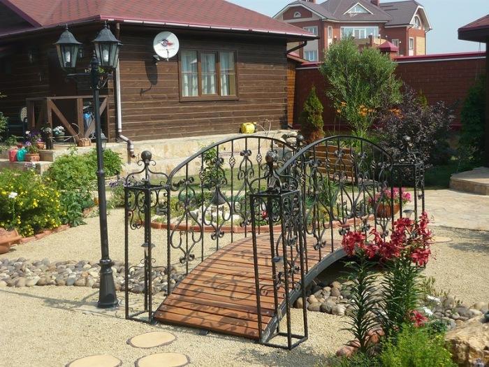 Декоративный кованый мостик, который отлично впишется в ландшафтный дизайн.