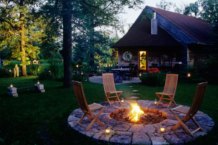 Необыкновенное каменное патио в тени деревьев с открытым очагом и простыми деревянными стульями идеально подойдет для любителей уединенного отдыха.