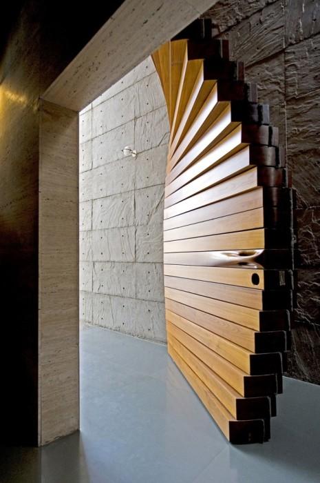 Массивная межкомнатная дверь изогнутой формы, созданная из деревянных брусков.
