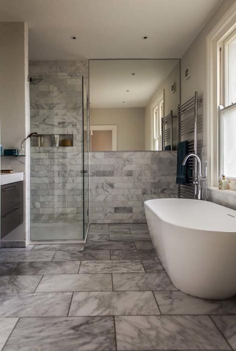 Декоративный камень, имитирующий мрамор в современном интерьере ванной комнаты.
