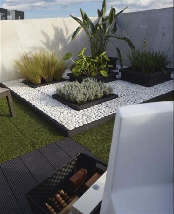 Композиция из гальки и необычных искусственных растений в профессионально оформленном ландшафтном дизайне.