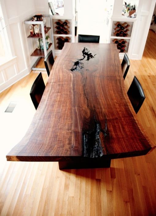 Эксклюзивный деревянный стол из темной породы древесины стал центром фокусировки внимания в комнате.