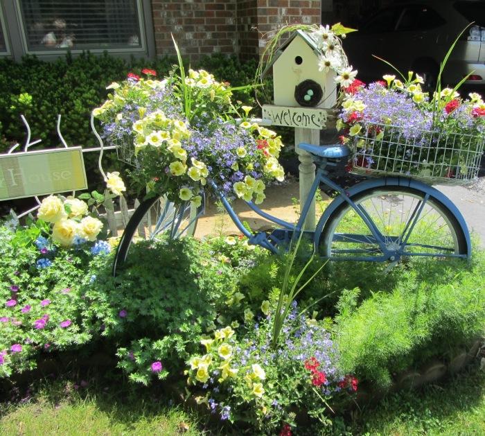 Старый велосипед может стать не только декоративным элементом в ландшафтном дизайне садового участка, но и оригинальным кашпо для небольших цветов и растений.