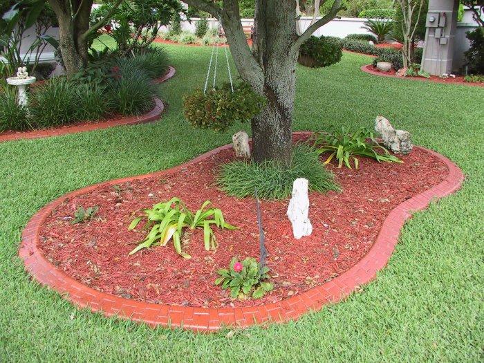 Красный кирпич, уложенный на сухую кладку вровень с газоном - доступное и функциональное решение.
