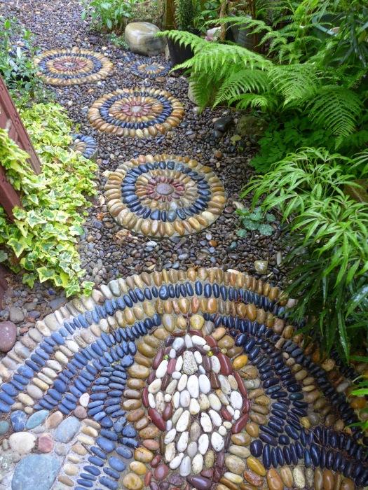 Мозаичное покрытие дорожек на садовом участке можно сделать из разбитых плиток или мелкой разноцветной гальки.