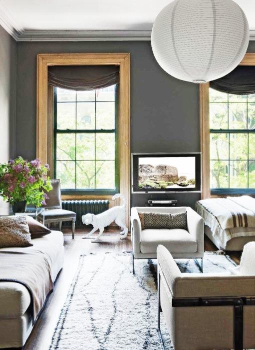 Просторная гостиная комната с современной мягкой мебелью и множеством деревянных деталей и элементов.