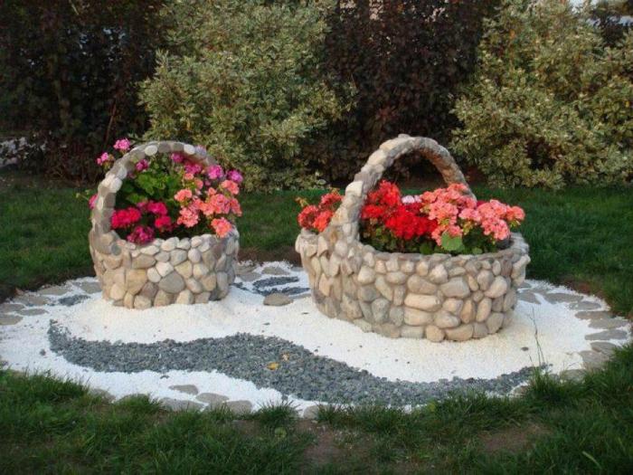 Каменные клумбы в виде корзин в интерьере садового участка.