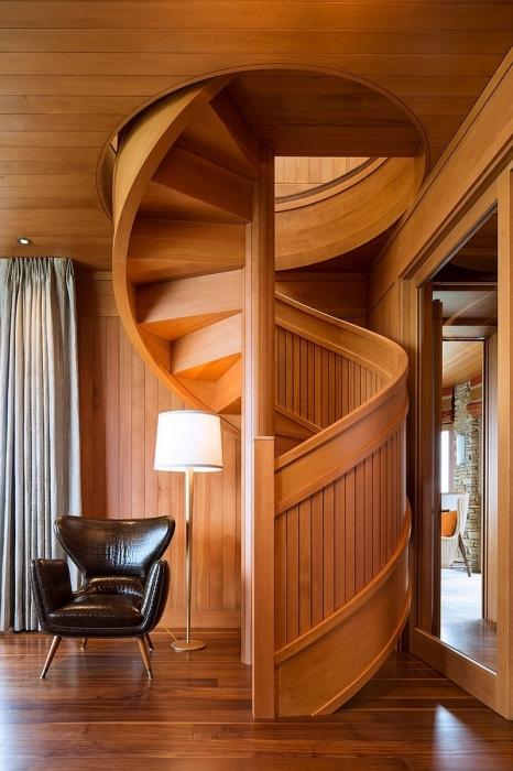 Небольшая спиралевидная лестница ведущая на второй этаж обшитая деревянными материалами.
