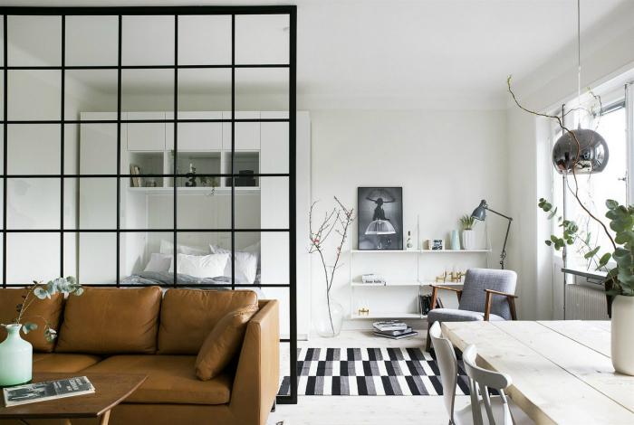Великолепная гостиная комната с белоснежным интерьером и стильной решетчатой перегородкой.