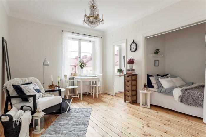 Восхитительный интерьер спальной комнаты с небольшой встроенной кроватью за шторками.