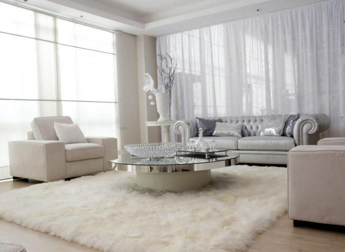 Небольшая светлая гостиная комната с ворсистым ковром, серым диванчиком и круглым журнальным столиком.