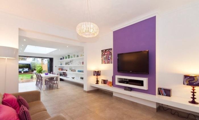 Просто покрашенная в фиолетовый оттенок стена в зоне для просмотра телевизора.