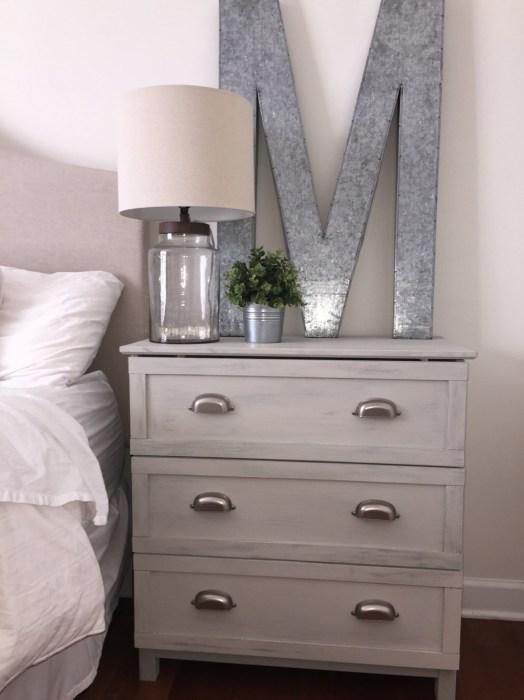 Классическая светлая деревянная тумбочка в интерьере спальной комнаты.