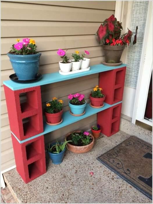 Стильные полочки для цветов в горшках, построенные из дерева и шлакоблоков, станут оригинальным украшением загородного участка.